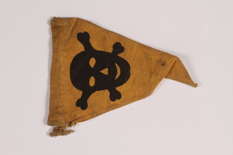 2014.461.4 front Yellow warning skull and crossbones pennant found by a concentration camp inmate after liberation