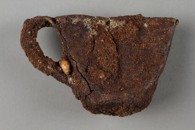1989.308.2 side b Rusted, crushed cup recovered from Chelmno killing center