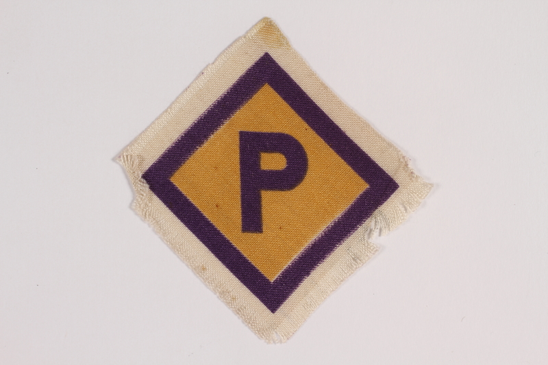 2014.469.2 front Forced labor badge, yellow with a purple P, worn by a Roman Catholic Polish youth