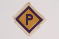 2014.469.2 front Forced labor badge, yellow with a purple P, worn by a Roman Catholic Polish youth  Click to enlarge