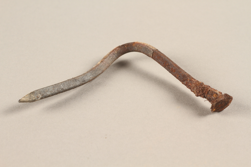 1989.308.28 side a Nail recovered from Chelmno killing center