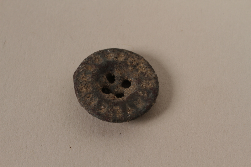 1989.308.4 front Small metal button recovered from Chelmno killing center