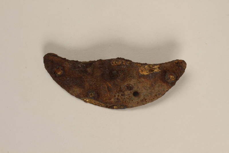 1989.308.6 front Rusted heel plate with screw recovered from Chelmno killing center