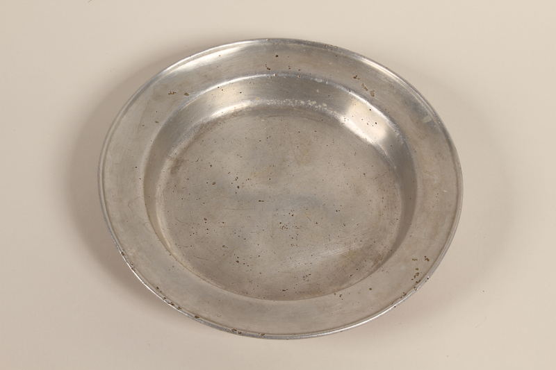 1996.128.1 front Metal plate used by an inmate of Dachau concentration camp