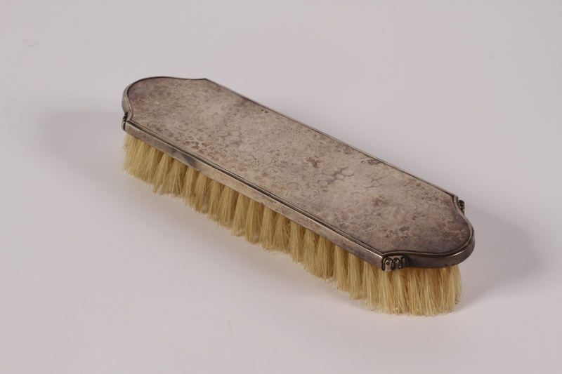 2005.600.3 front Silver clothes brush used by a German Jewish woman while in hiding