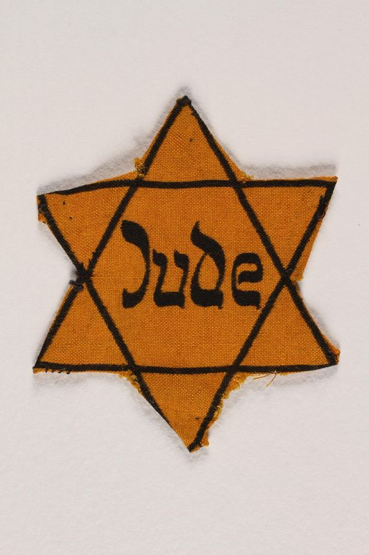 1996.23.73 front Yellow cloth Star of David badge with the word Jude