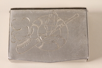 1996.49.1 front Metal box made by a slave laborer and engraved with camp names  Click to enlarge