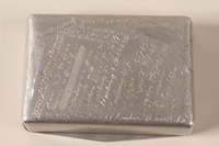 1996.49.1 back Metal box made by a slave laborer and engraved with camp names  Click to enlarge