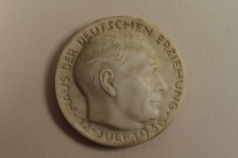 """1996.75.15 front Nazi badge, """"House of German Education"""""""