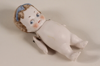 1996.76.1 front Small white tinted all bisque doll brought by a German Jewish girl to Theresienstadt  Click to enlarge