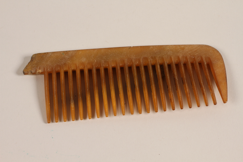 1997.31.2.1 front Golden-brown comb owned by a Lithuanian Jewish concentration camp inmate