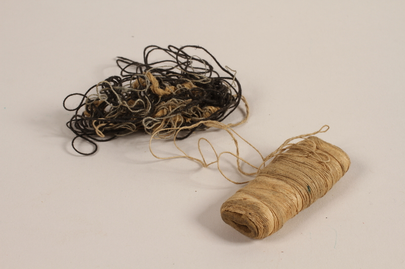 1997.31.2.4 front Tan spool and black loose thread used by a Lithuanian Jewish concentration camp inmate