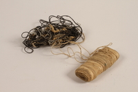 1997.31.2.4 front Tan spool and black loose thread used by a Lithuanian Jewish concentration camp inmate  Click to enlarge