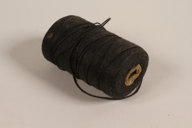 1997.31.2.5 front Spool of black thread used by a Lithuanian Jewish concentration camp inmate