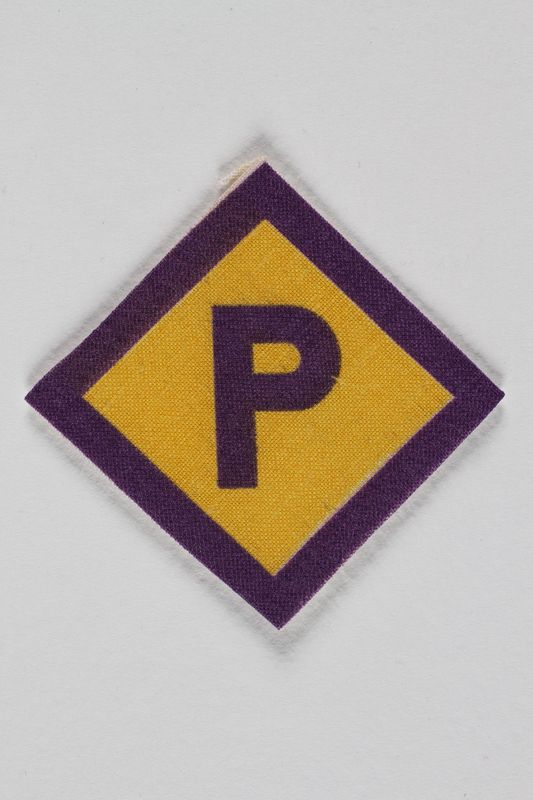 1997.67.1 front Forced labor badge, yellow with a purple P, to identify a Polish forced laborer