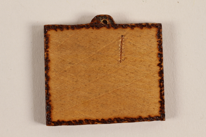 1989.342.1 back Small wooden tile with the Terezin church steeple made by a former Jewish Czech concentration camp inmate