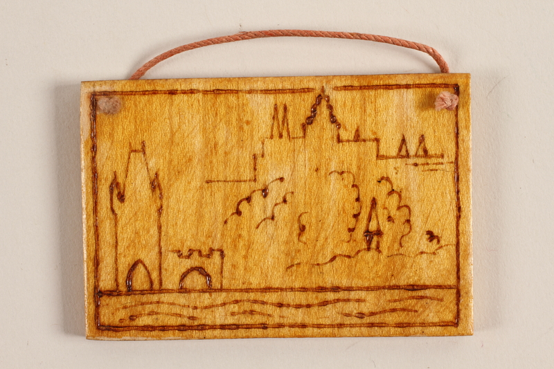1989.342.13 front Small wooden ornament with on outline of a town made by a former Jewish Czech concentration camp inmate