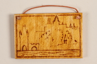 1989.342.13 front Small wooden ornament with on outline of a town made by a former Jewish Czech concentration camp inmate  Click to enlarge