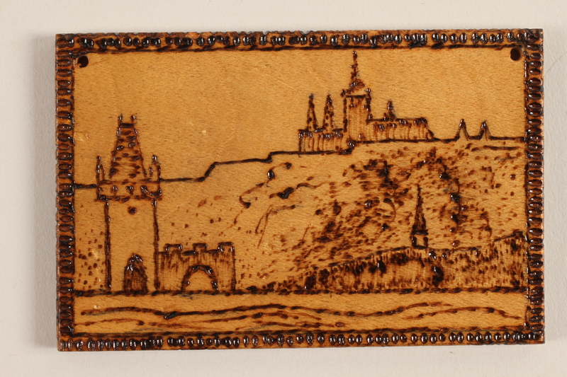 1989.342.14 front Small wooden ornament with a view of a hillside town made by a former Jewish Czech concentration camp inmate