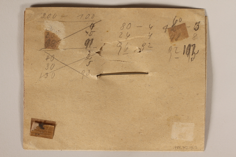 1989.342.15.1-.2 back Pin with a cutout image of the Small Fortress gate at Terezin pinned to paper made by a camp inmate