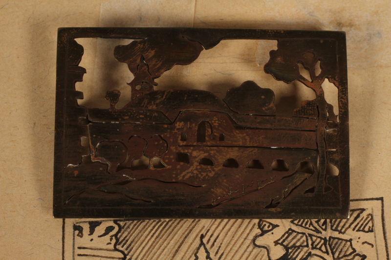 1989.342.15.1 front Pin with a cutout image of the Small Fortress gate at Terezin pinned to paper made by a camp inmate