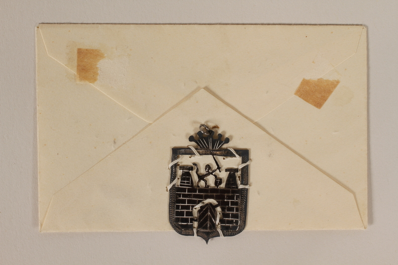 1989.342.16.1-.2 front Cutout pendant of the Terezin coat of arms sewn to an envelope made by a former Jewish Czech inmate