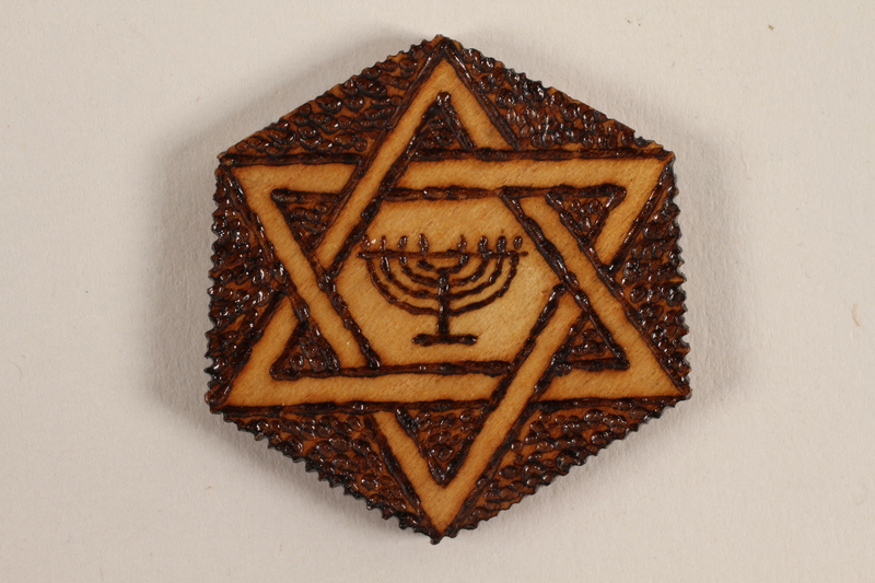 1989.342.3 front Small hexagonal wooden tile with a Star of David and menorah made by a former Jewish Czech inmate