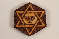 1989.342.3 front Small hexagonal wooden tile with a Star of David and menorah made by a former Jewish Czech inmate  Click to enlarge
