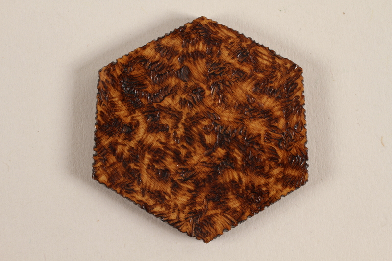1989.342.3 back Small hexagonal wooden tile with a Star of David and menorah made by a former Jewish Czech inmate