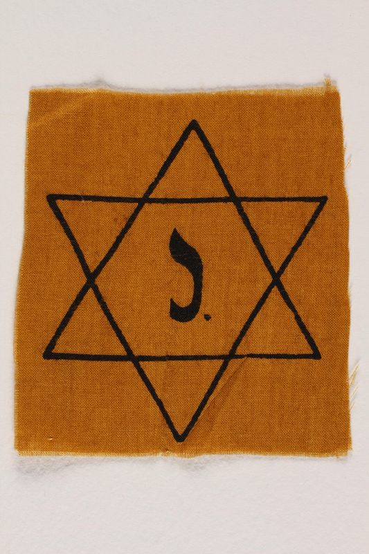 1998.118.1 front Yellow cloth Star of David badge with the letter J. to identify a Belgian Jew