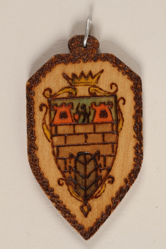 1989.342.9 front Small colored wooden pendant with Terezin crest made by a former Jewish Czech concentration camp inmate