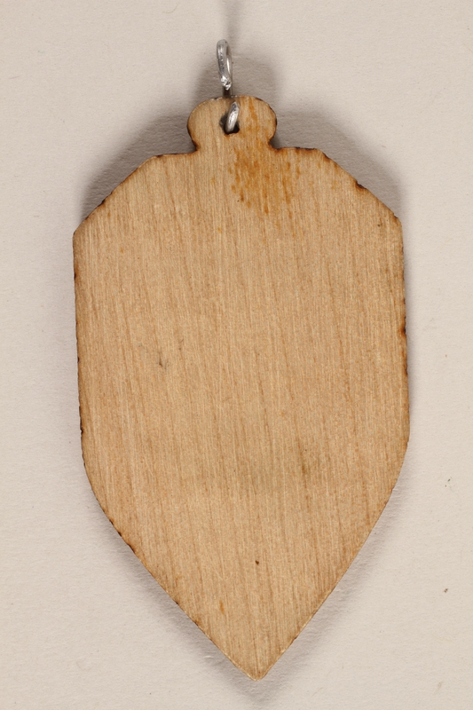 1989.342.9 back Small colored wooden pendant with Terezin crest made by a former Jewish Czech concentration camp inmate