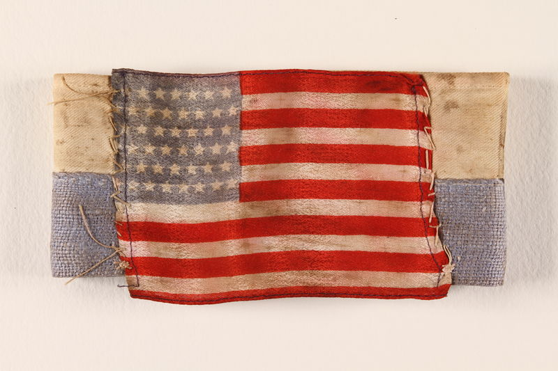 1999.168.7 front Blue and white striped armband with a US flag patch
