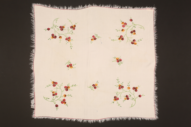 2000.270.1 front Doily with embroidered yellow, red, and pink flowers recovered postwar by a Polish Jewish girl