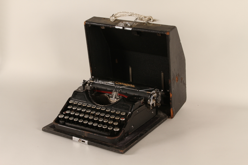 2000.281.1_a-b front Continental typewriter with a swastika and SS emblem key and a removable lid