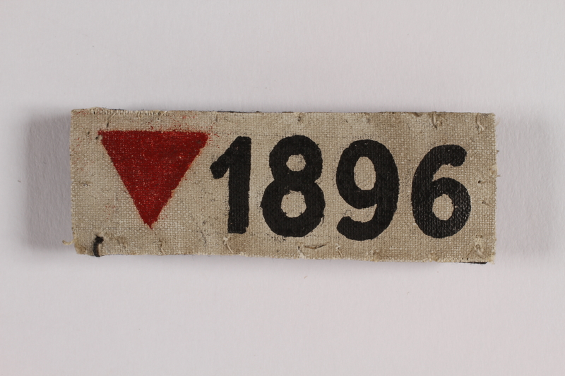 2012.482.1 front White badge with an inverted red triangle and number 1896 worn by a gay concentration camp inmate