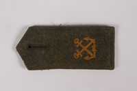 2014.480.64 front Olive shoulder board with gold crossed swords acquired by US soldier  Click to enlarge