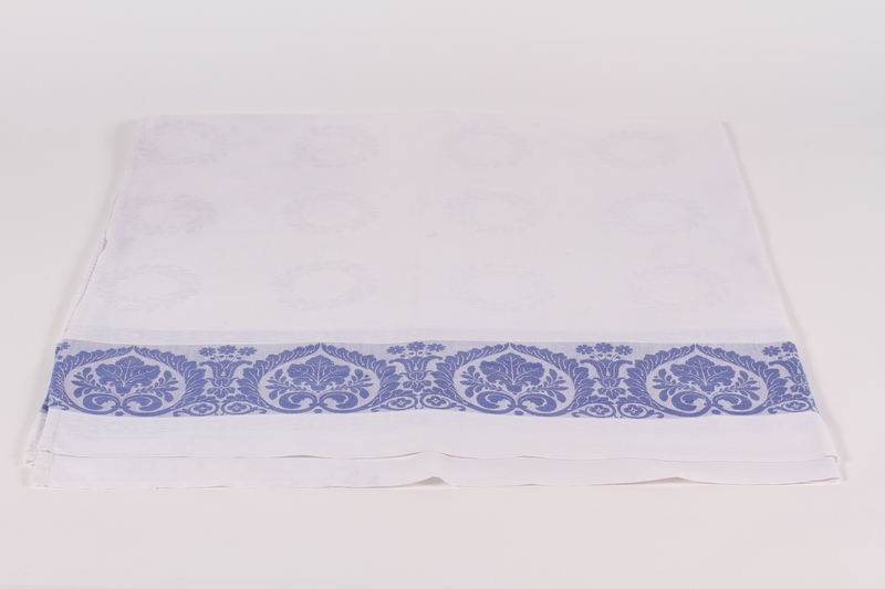 2014.490.3 front Embroidered tablecloth with blue floral design owned by a Jewish woman