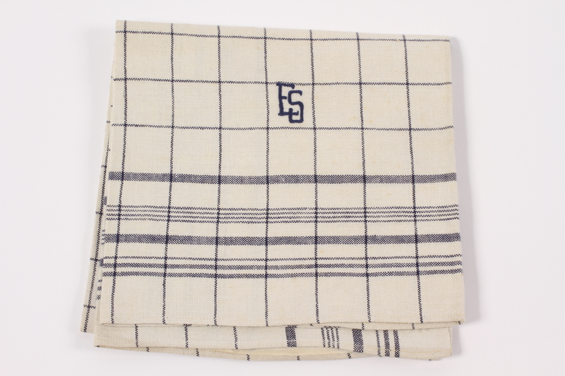2012.485.6 front Black checked towel embroidered ES saved by German Jewish refugees