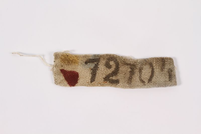 2014.497.2 front White cloth badge with his prisoner number owned by a Belgian Jewish man deported to slave labor camps