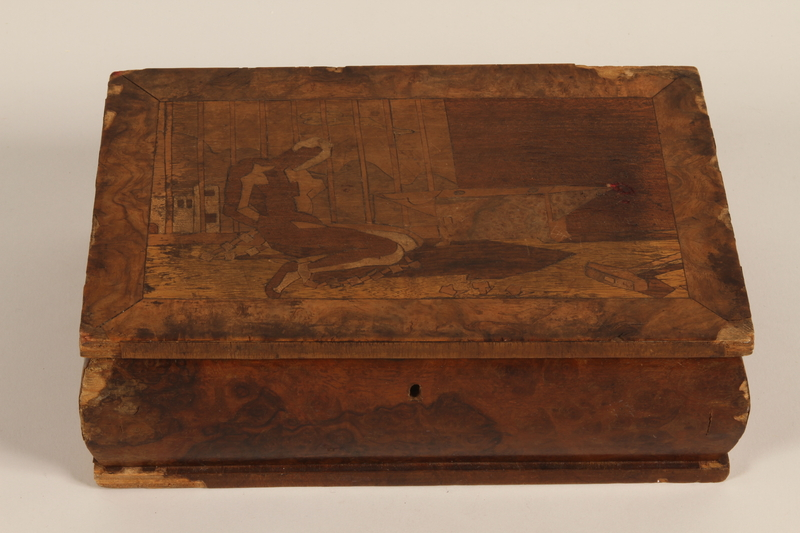 1991.152.1 closed Wooden box with a decorative inlay of a figure