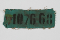 1994.50.1 front Green prisoner badge with the number 107668  Click to enlarge