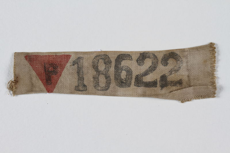 1998.134.7 front Prisoner badge with red triangle and number