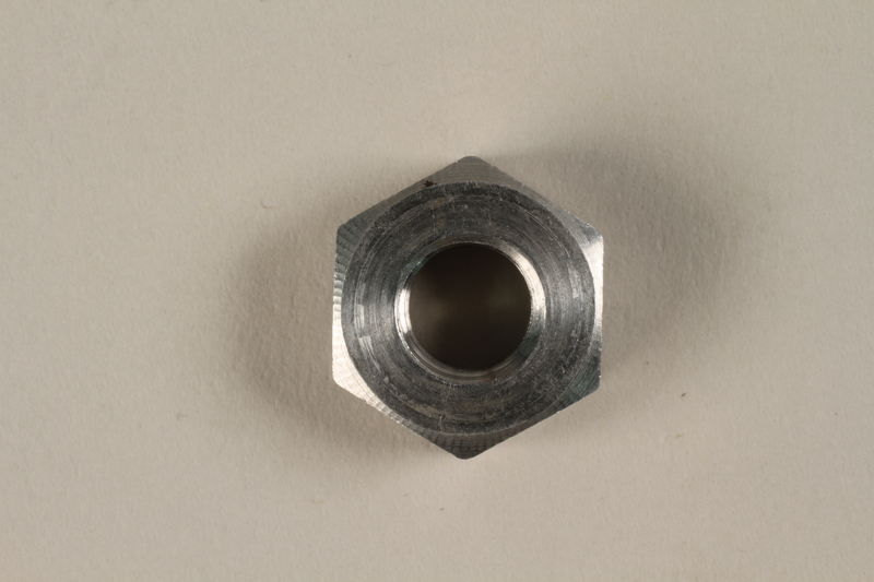 1990.203.3 front Aluminum nut found in a tunnel at Nordhausen by a US soldier