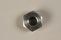 1990.203.3 front Aluminum nut found in a tunnel at Nordhausen by a US soldier  Click to enlarge