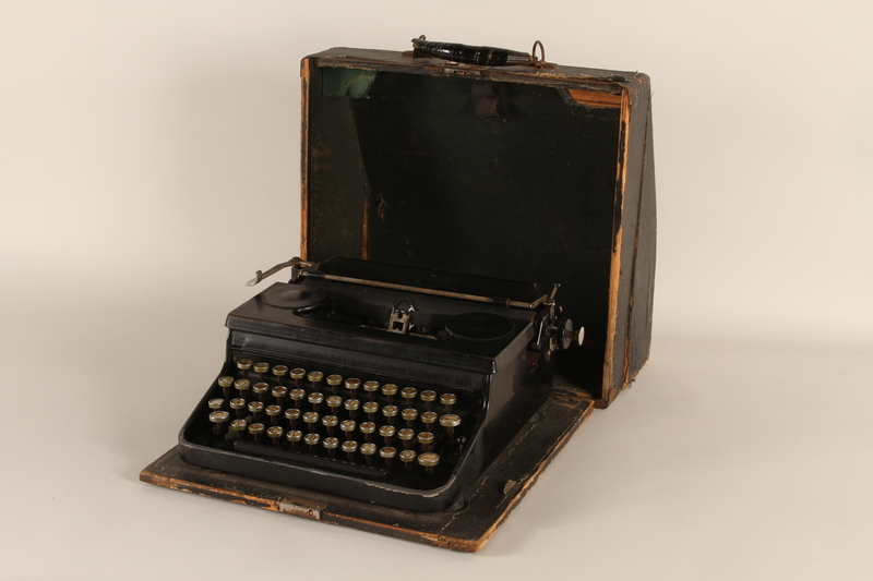 1990.213.1_a-b front Black metal typewriter with case used by a Hungarian rescuer to forge documents