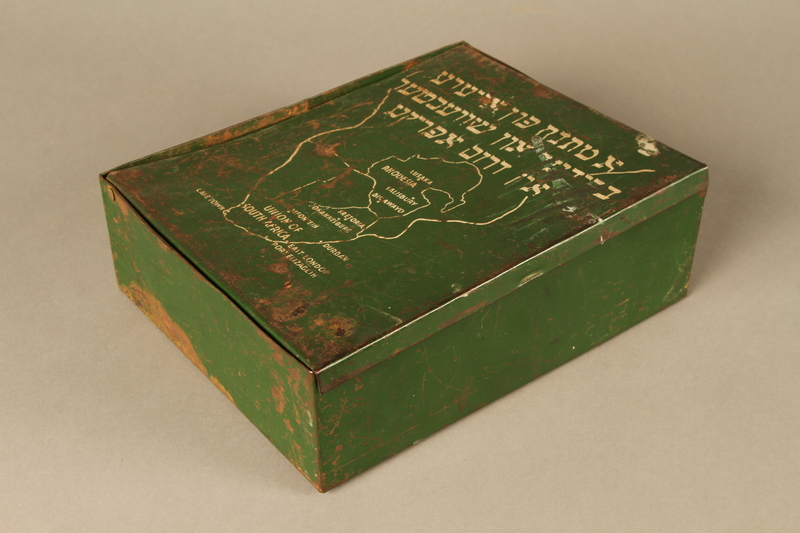 1999.333.1 3/4 closed School supply metal box inscibed in Yiddish