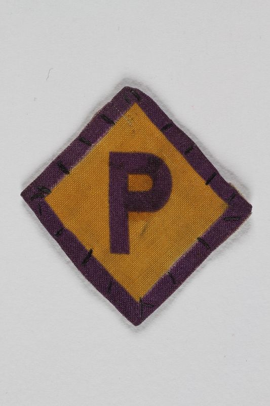 1990.259.2 front Forced labor badge, yellow with a purple P, worn by a Polish Catholic kidnapped into forced labor service