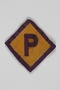 Forced labor badge, yellow with a purple P, worn by a Polish Catholic kidnapped into forced labor service
