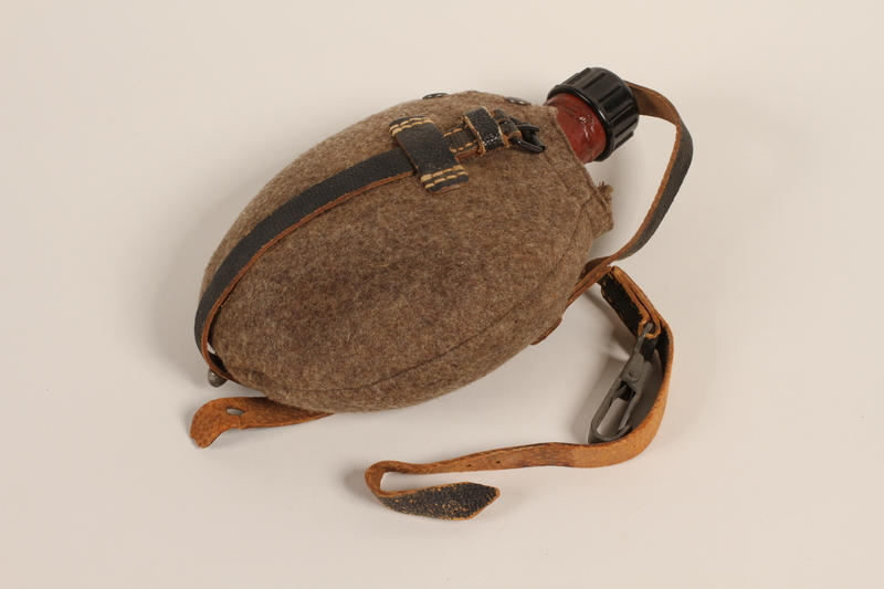 1985.1.1 front German military red painted canteen in pouch with strap acquired by US soldier